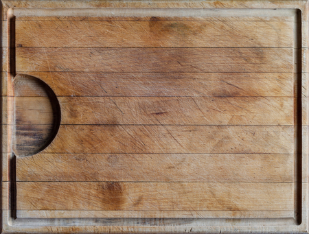 cut: Rough wooden rectangular used cutting board background with horizontal lines and cutting traces directly from above