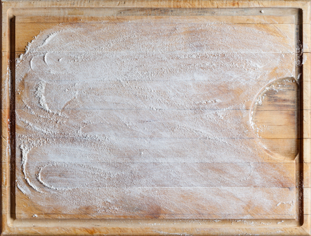 Rough wooden rectangular used cutting board background with flour directly from above