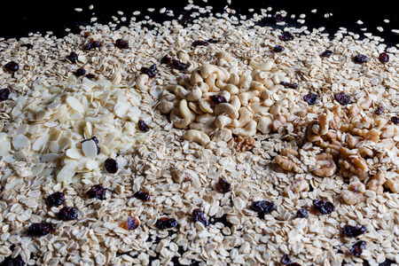 flaked: Granola ingredients oatmeal flaked almonds shelled walnuts and cashew on black background from side Stock Photo