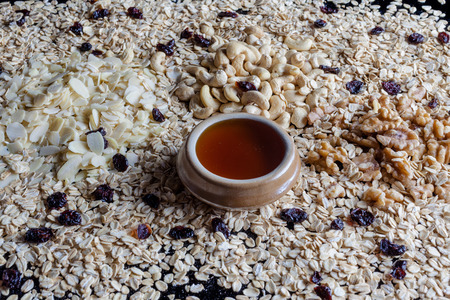 flaked: Granola ingredients oatmeal flaked almonds shelled walnuts and cashew with cup of honey from side Stock Photo