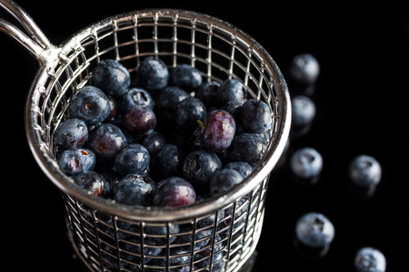 high angle: Blueberries in steel cup strainer on black background from side high angle