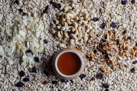 directly above: Granola ingredients oatmeal flaked almonds shelled walnuts and cashew with cup of honey directly above