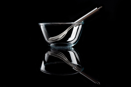 whisker: Glass transparent bowl with metal whisker inside on black background side view with reflection
