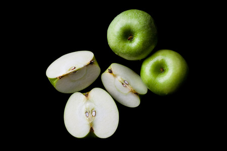 directly: Two whole green apples and one sliced on black background directly from above Stock Photo