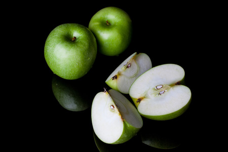 horizontal  green: Two whole green apples and one sliced on black background directly from side high angle with reflection