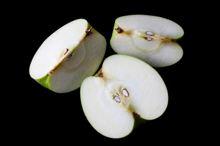 directly: Sliced green apple half and two quarters on black background directly from above