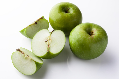 high angle: Two whole green apples and one sliced on white background directly from side high angle with reflection Stock Photo