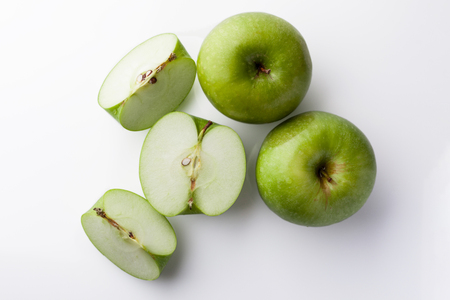 directly: Two whole green apples and one sliced on white background directly from above