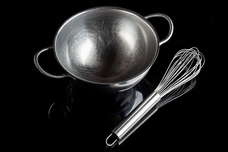 whisker: Stainless steel bowl with metal whisker aside on black background from high angle with reflection