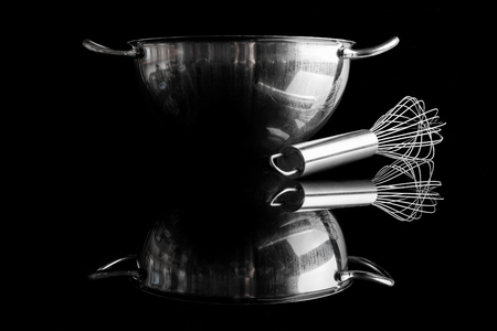 whisker: Stainless steel bowl with metal whisker aside on black background from side with reflection Stock Photo