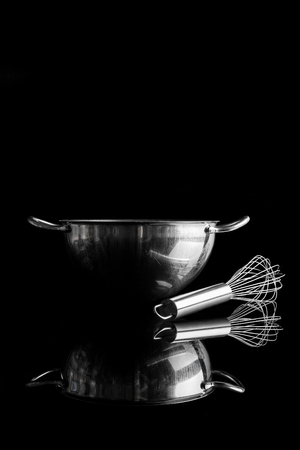 whisker: Stainless steel bowl with metal whisker aside on black background from side with reflection vertical composition