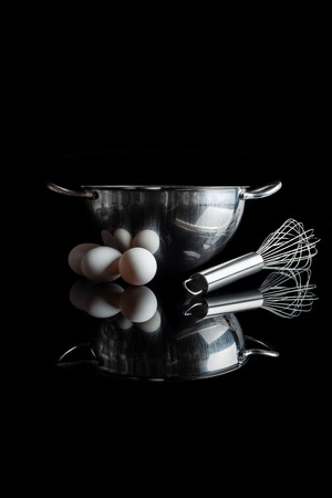 whisker: Stainless steel bowl with metal whisker and three white eggs aside side view with reflection on black background vertical