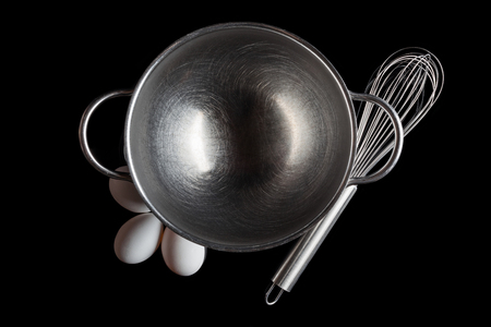 whisker: Stainless steel bowl with metal whisker and three white eggs aside directly from above on black background Stock Photo