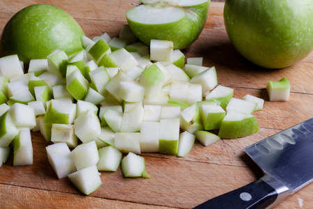 granny smith: Cut granny smith green apples on wooden cutting board with knife from side