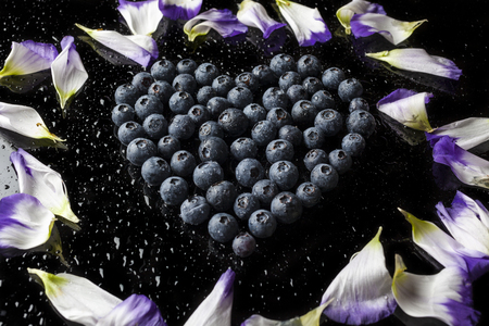 Blueberries heart with water drops and purple and white flower blueberries heart with water drops and purple and white flower petals from high angle on black mightylinksfo