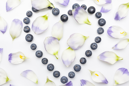 directly: Blueberries hollow heart with flower petals directly from above on white background
