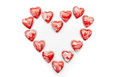 directly: Red and white heart shaped chocolates arranged in heart on white background directly from above