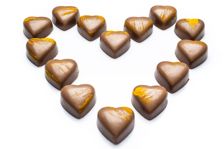high angle: Milk heart shaped chocolates with yellow embellishment arranged in heart on white background from high angle Stock Photo