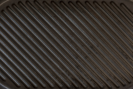 griddle: Black used rough cast iron griddle grill pan ribbed background