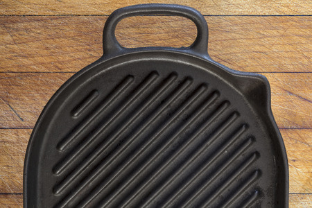 cast iron: Black used rough cast iron griddle grill pan on wooden table background
