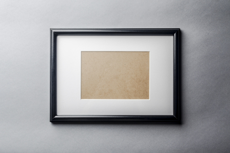 passepartout: Black plain empty thin wood picture frame with white mat passe-partout on grey wall background