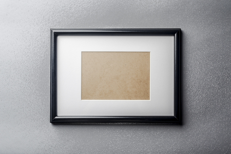 passepartout: Black plain empty thin wood picture frame with white mat passe-partout on grey textured glass wall background