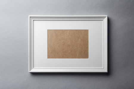 passepartout: White plain empty wood picture frame with white mat passe-partout on grey wall background Stock Photo