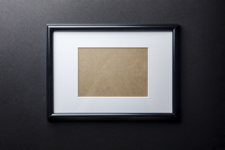 passepartout: Black thin plain empty wood picture frame with white mat passe-partout on black wall background