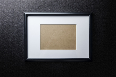 passepartout: Black plain empty thin wood picture frame with white mat passe-partout on black rough paint wall background