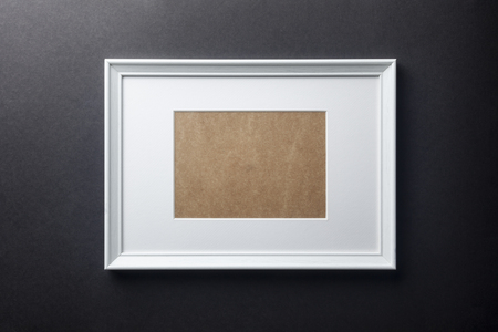 passepartout: White plain empty wood picture frame with white mat passe-partout on black wall background