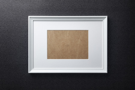passe: White plain empty wood picture frame with white mat passe-partout on black rough textured wall background