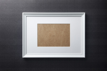 passepartout: White plain empty wood picture frame with white mat passe-partout on black bricks background
