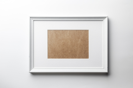 White plain empty wood picture frame with white mat passe-partout on white wall background