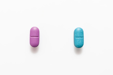 Pink pill and blue pill on white background from above