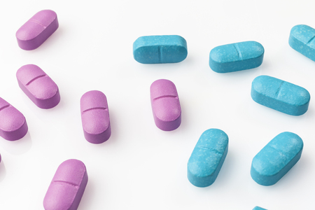 scattered on white background: Scattered pink and blue pills on white background from high angle closeup