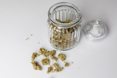scattered on white background: Medical cannabis buds in an open glass jar with marijuana flowers scattered aside and transparent lid on white background from high angle