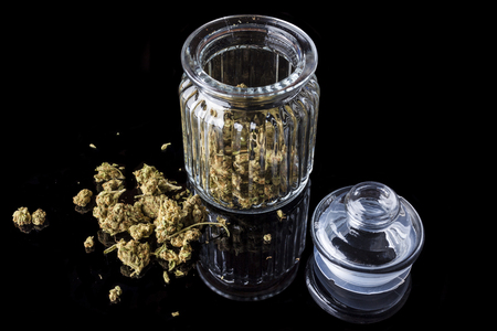 relaxant: Medical cannabis buds in an open glass jar with marijuana flowers scattered aside and transparent lid on black background from high angle Stock Photo