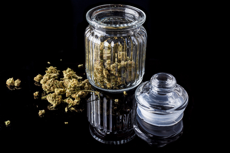 Medical cannabis buds in an open glass jar with marijuana flowers scattered aside and transparent lid on black background from side
