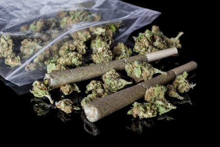 relaxant: Pile of medical cannabis dried buds scattered from nylon package and two marijuana joints on black background from side