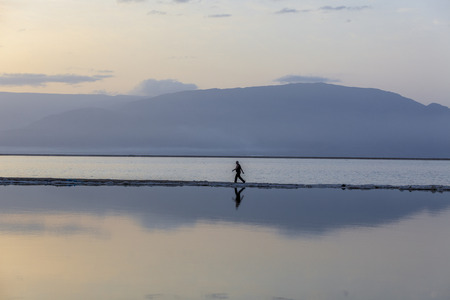 headland: Man wearing black sports clothes walking on headland at the Dead Sea in early blue morning with mountains background