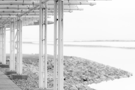 greyscale: Early morning black and white view from dock with white pillars on Dead Sea waters