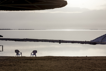 retreats: Two white plastic chairs and sunshades at lonely beach in the early morning Stock Photo