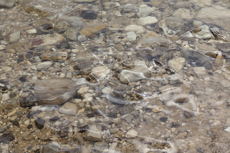 boulders: Grey yellow brown black boulders under water background