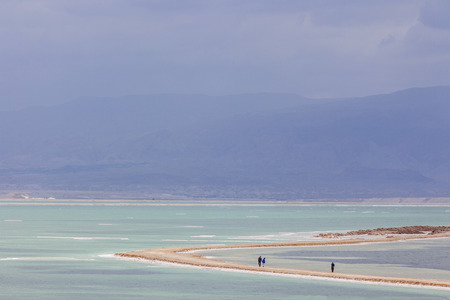 headland: Three people walking on headland between the turquoise waters on dark stormy day at Dead Sea with mountains on background Stock Photo