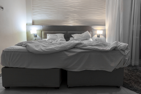 switched: Double messed brown bed with white linen in a hotel room with the night lights switched on beside the bed