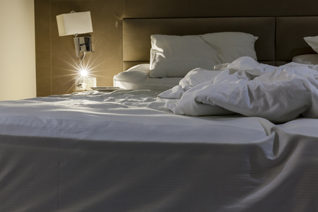 messed: One side of double messed bed with white linen with reading light turned on and notebook with pen beside the pillow