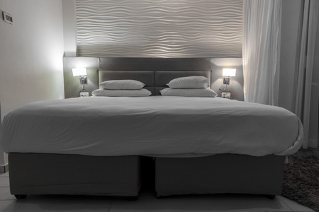 switched: Double set up brown bed with white linen in a hotel room with the night lights switched on beside the bed