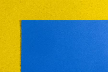 eva: Eva foam ethylene vinyl acetate smooth blue surface on lemon yellow sponge plush background Stock Photo