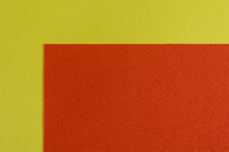 eva: Eva foam ethylene vinyl acetate sponge plush orange surface on lemon yellow smooth background Stock Photo