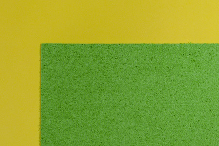 acetate: Eva foam ethylene vinyl acetate sponge plush apple green surface on lemon yellow smooth background Stock Photo